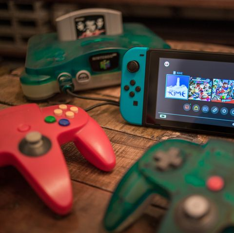 a vintage n64 console pictured with multiple controllers and a nintendo switch