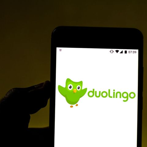 In this photo illustration the Duolingo logo is displayed on...