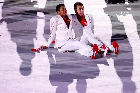 una pareja de indonesios observa sentada en el suelo el desfile