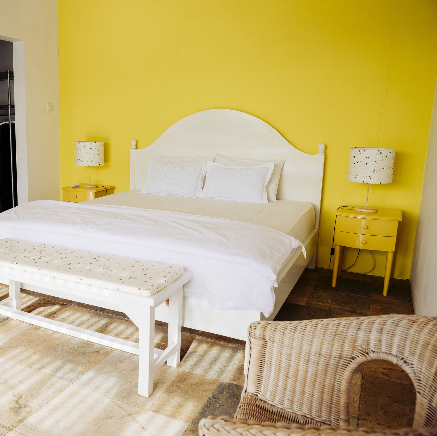 Indonesia, Bali, bedroom with yellow wall and yellow bedside cabinets of a holiday villa