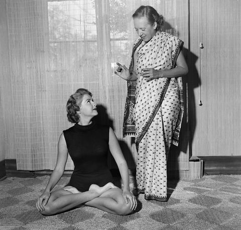 indra devi instructs a student on a yoga position in her hollywood studio in 1952