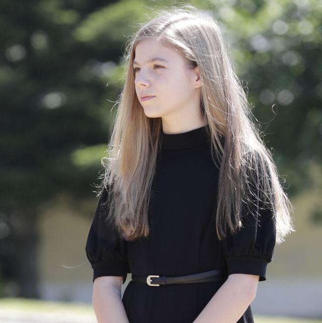 la hija de los reyes, con un vestido negro, posa en un jardín