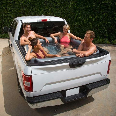 group of adults sitting in an inflatable pool in a pickup truck's cargo bed