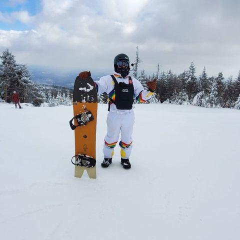 man holding snowboard on snowy mountain
