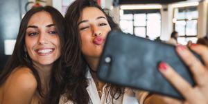 Portrait of two friends taking selfie with smartphone in a coffee shop having fun