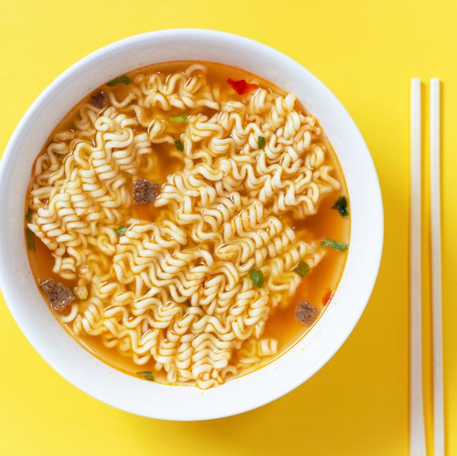 instant noodle soup in a white bowl on yellow background top view