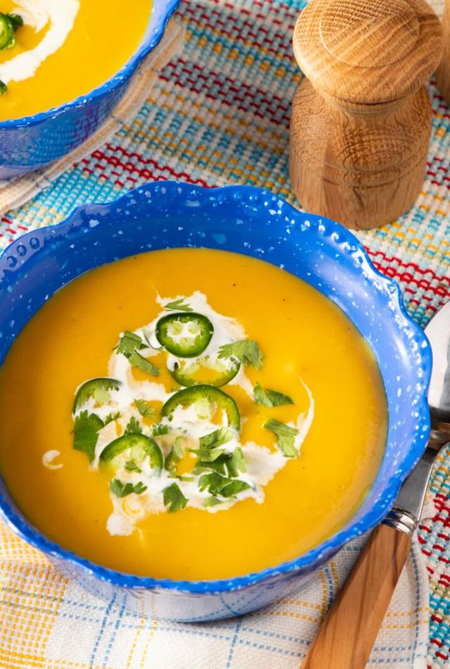 instant pot butternut squash soup with coconut milk cilantro and jalapeno in a blue bowl with salt and pepper shaker