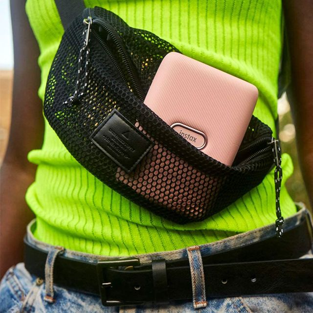 young person holding instax printer in fanny pack