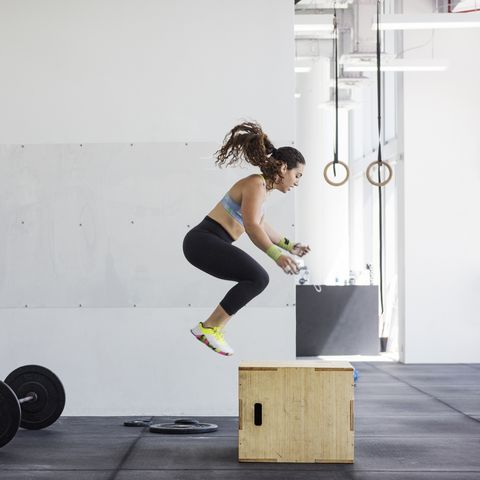Instructor photographing athlete exercising on jump box in crossfit gym