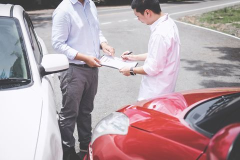 Insurance Agent And Customer With Document Standing By Cars On Road