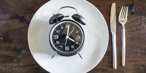 Intermittent fasting, trend 16:8 fasten, alarm clock on plate