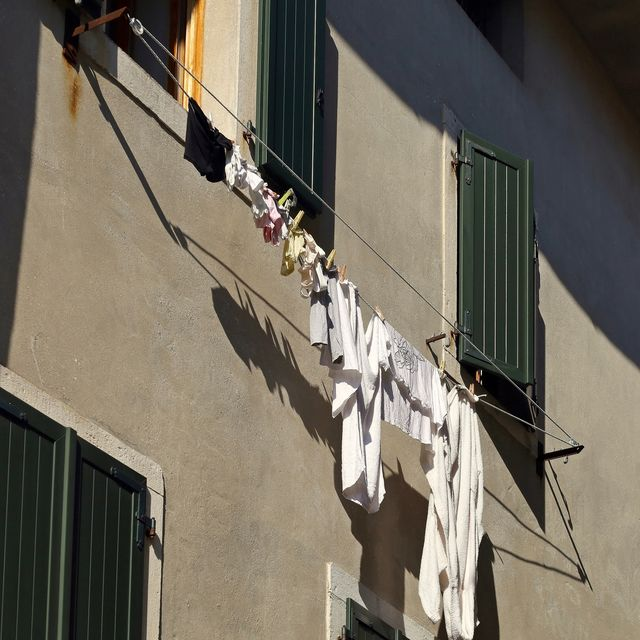 white laundry and underwear hanging out to dry on the drying rack between two home windows in italy