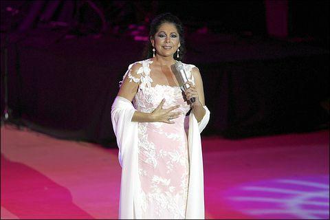 isabel pantoja cantando sobre un escenario con un vestido blanco