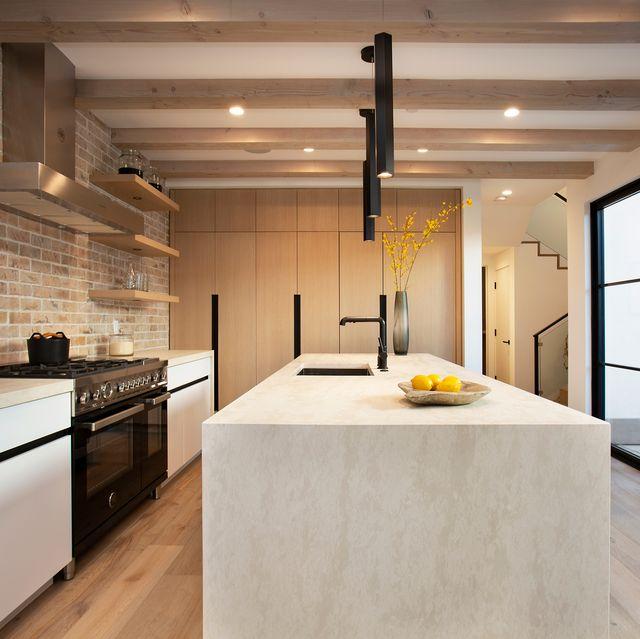cocina abierta con isla central y pared de ladrillo visto