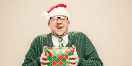 Nerdy Guy with Christmas Gift and Santa Hat