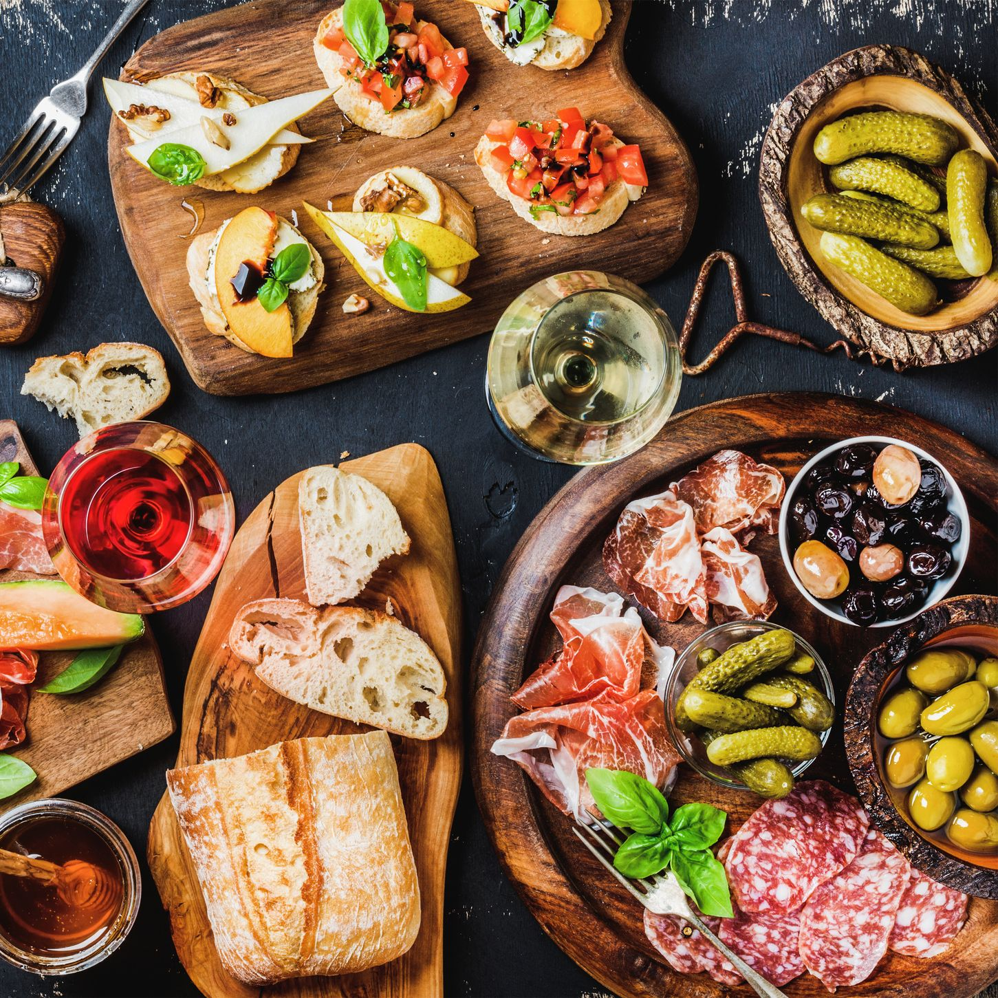 Italian antipasti wine snacks set over black grunge background