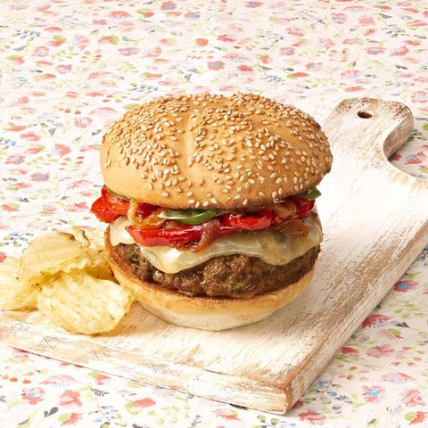 sausage and peppers burgers with potato chips on wood board