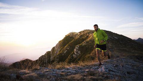 Italy, man running on mountain trail