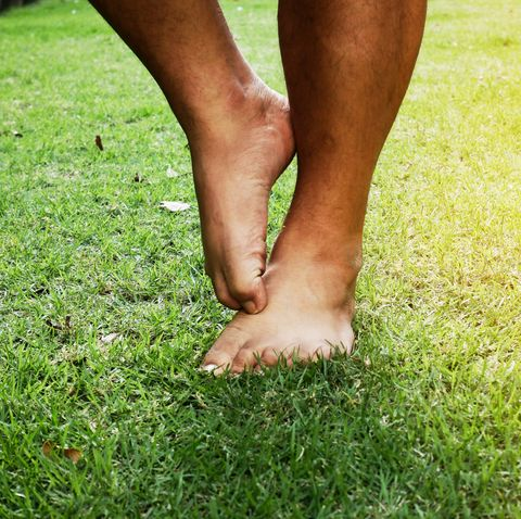 Itching from athlete's foot on grass in the park.