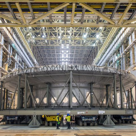a photo shows two tiny people standing in front of a gigantic, cylindrical casing for the iter project's tokamak