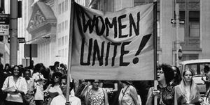 Signs saying Women Unite carried by wome