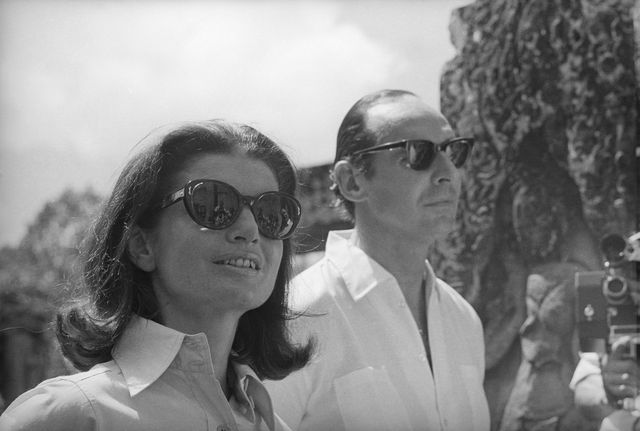 original caption wearing sunglasses jacqueline kennedy and her escort, lord harlech of great britain, tour the ruins of the bayon temple, a 16 spired citadel of the ancient khmer empire mrs kennedy and lord bayon later picnicked and toured the ruins of angkor wat, fulfilling a dream she has had since college days