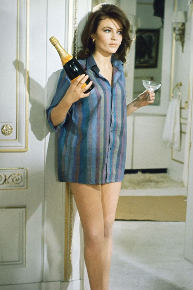 jacqueline bisset, british actress, wearing a shirt with vertical stripes, and holding a bottle of champagne and a champagne coupe, in a publicity still issued for the film, 'bullitt', 1968 the thriller, directed by peter yates 1929 2011, starred bisset as 'cathy' photo by silver screen collectiongetty images