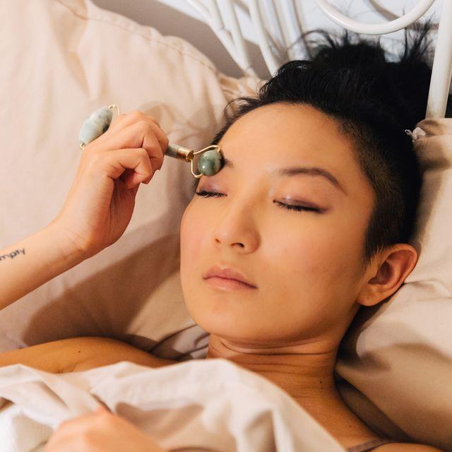woman using jade roller in bed