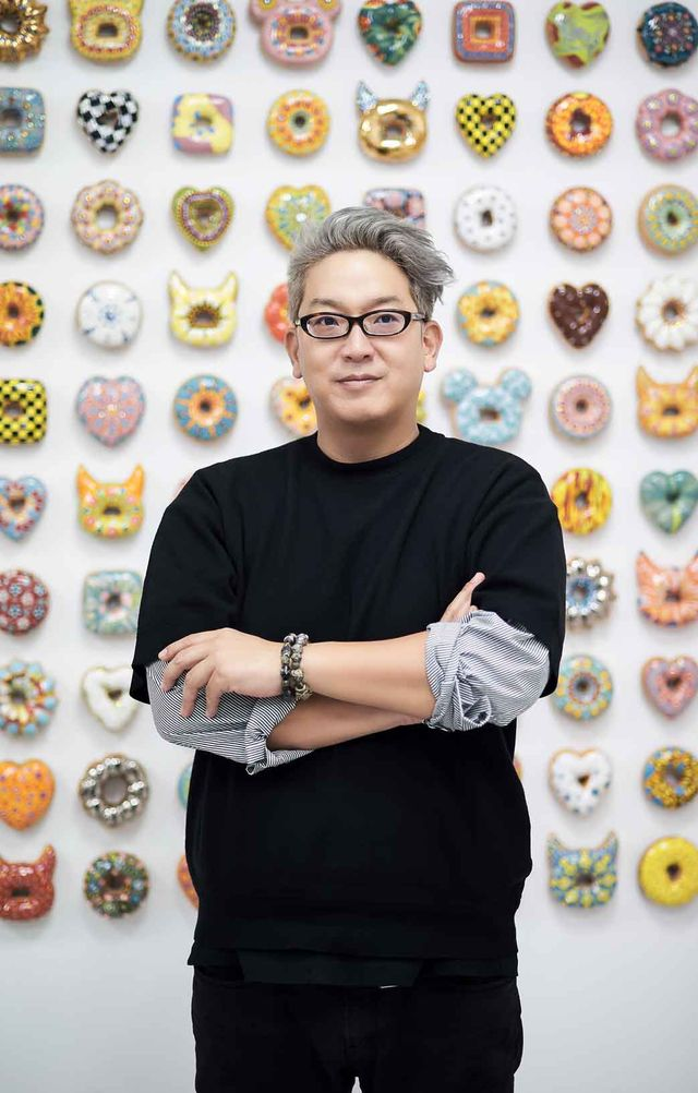 man in front of donut wall
