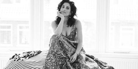 Styliste Ramona Da Cruz Lopes op een berg van haar eigen kleding