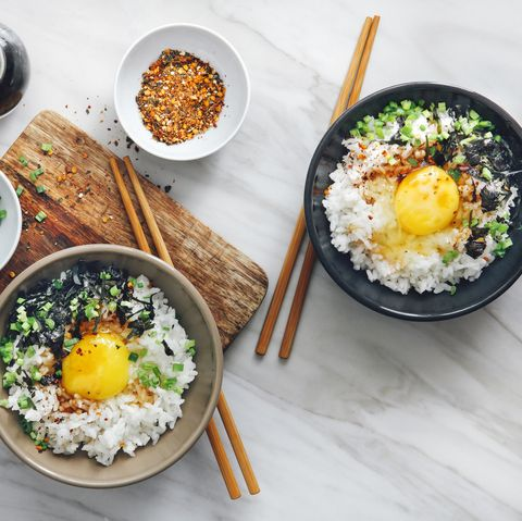 overhead shot of bowls of Asian cuisine with rice and chopsticks