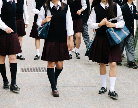 Japanese high school. School children walk outside, unrecognisable, school uniform