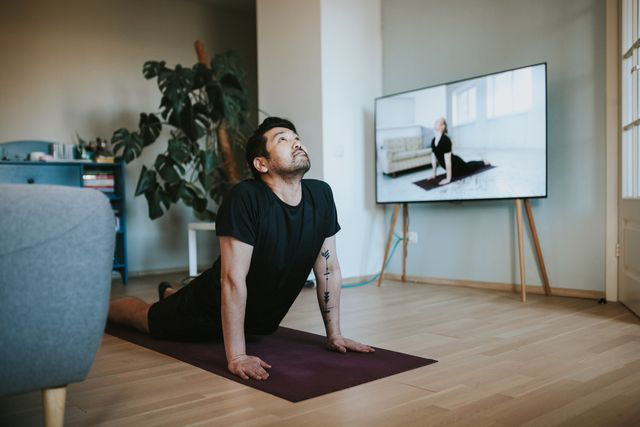 japanese man taking online yoga lessons during lockdown in isolation