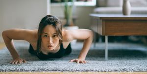 Japanese woman in fitness attire performing push-ups on floor of living room
