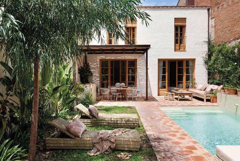 jardín con piscina y tumbonas de fibra trenzada