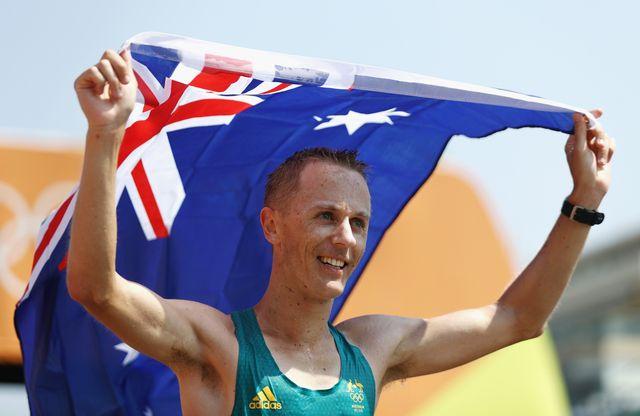 jared tallent celebra una medalla olímpica en marcha debajo de una bandera de australia