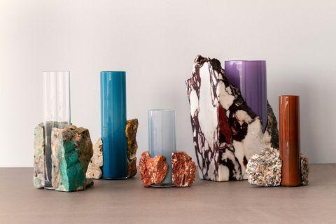 jarrones de diseño erik olovsson con la base de piedra y en la parte superior, un cilindro de vidrio con distintas combinaciones y colores