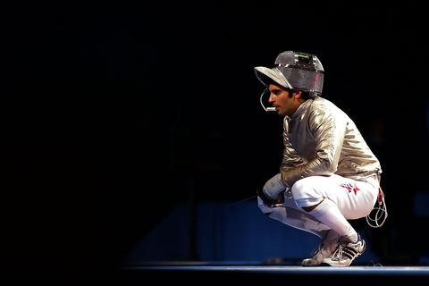 jason rogers squatting in his fencing gear at the beijing olympics