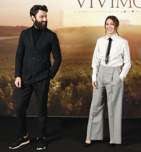 el actor, con traje negro, mira hacia donde se encuentra su novia, con pantalón, camisa y corbata