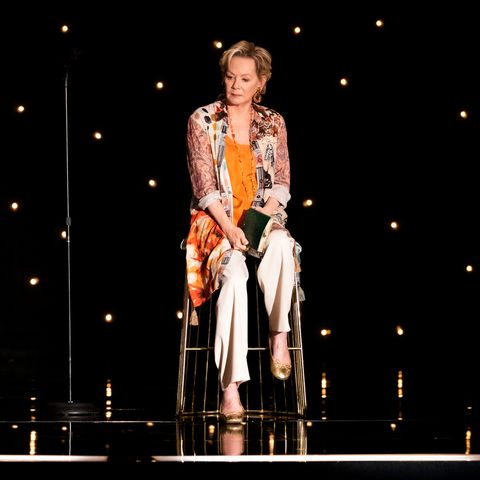 jean smart wearing an orange shawl and white pants sitting on a stage in her new show hacks