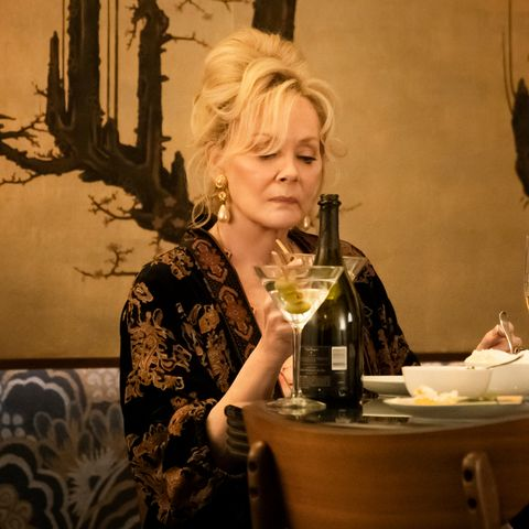 jean smart in a animal print blouse drinking a martini