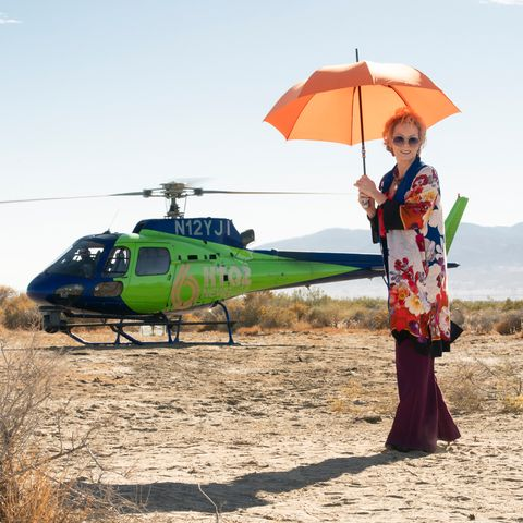 jean smart with a parasol about to board a helicopter