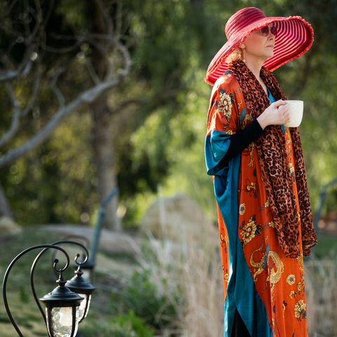 jean smart in a red sunhat and flowing orange sweater