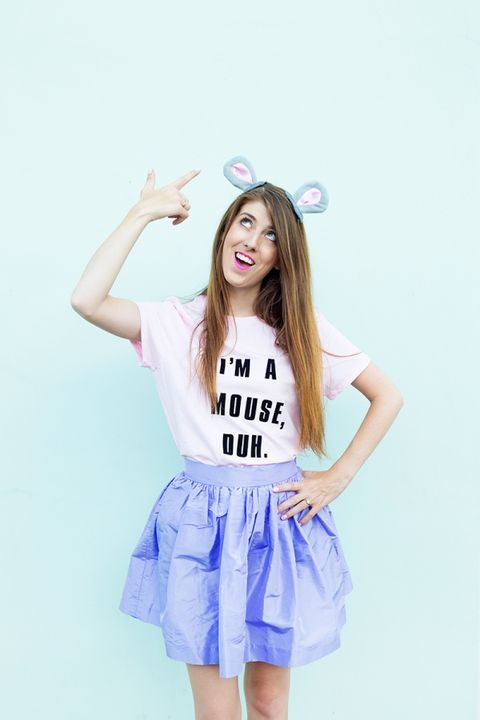 woman in blue ruffled skirt pointing to costume mouse ears on her head, wearing t shirt that says, i'm a mouse, duh