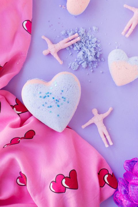 heart shaped bath bombs scattered against a purple background with a pink and red heart scarf and little toy men