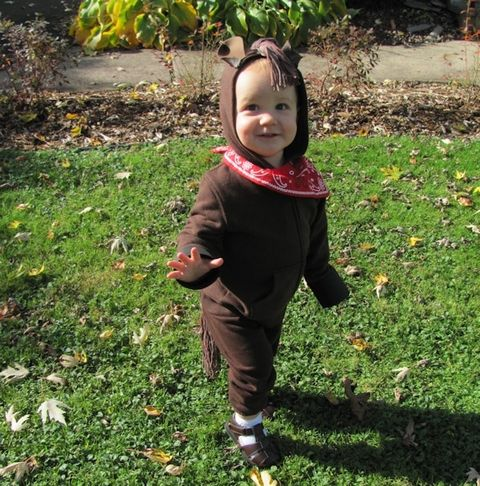 child dressed as horse in brown hooded sweatshirt and pants with a red bandana around neck the hood has a mane made of yarn and brown felt ears