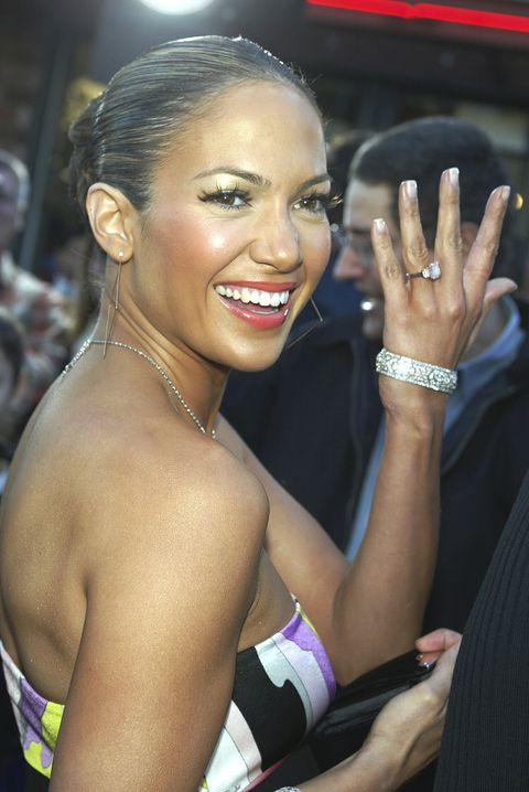 los angeles   february 9  actresssinger jennifer lopez shows fans her engagement ring as she arrives at the premiere of daredevil at the village theatre on february 9, 2003 in los angeles, california photo by kevin wintergetty images