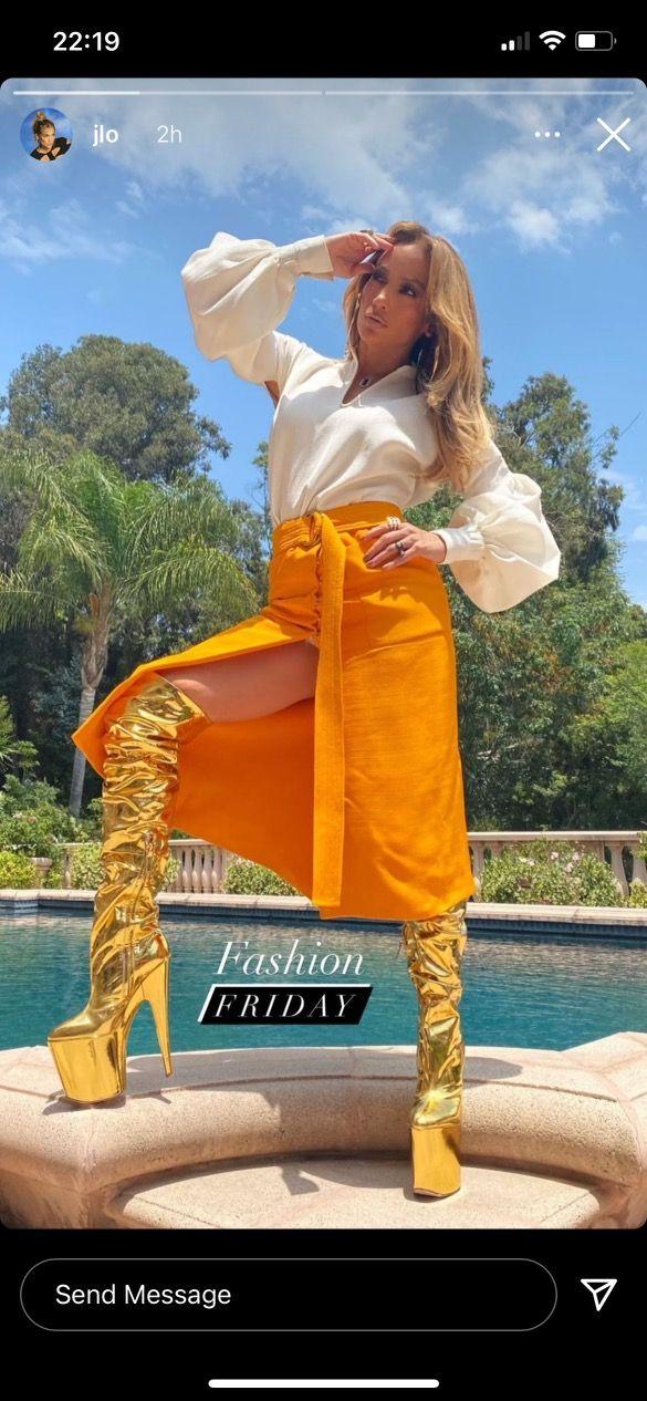 Jennifer Lopez Stuns in an Orange Skirt With a Thigh-High Leg Slit and Gold Platform Boots