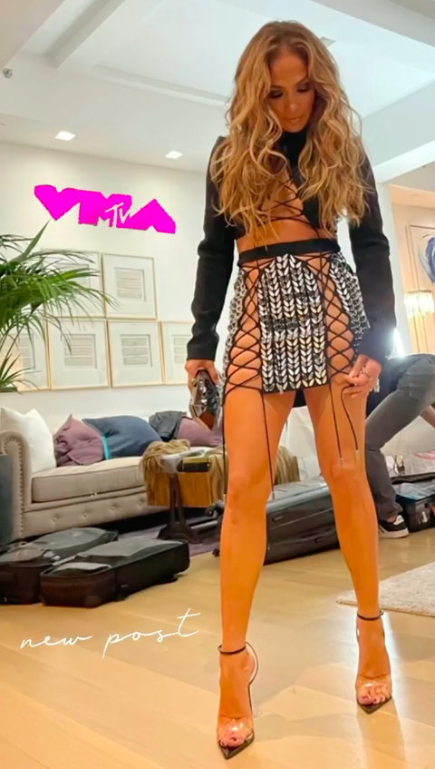 Jennifer Lopez at the 2021 MTV Video Music Awards with a crystal miniskirt, crop top and long hair with lots of volume delivers the song of the year award