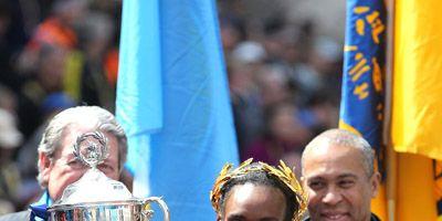 Rita Jeptoo hoists winner's cup after 2014 Boston Marathon